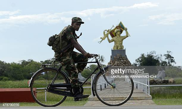 A Sri Lankan Army soldier rides a bicycle past a memorial for the Sri Lankan Army in the northern district of Mullaittivu on May 17 2015 The sixth...