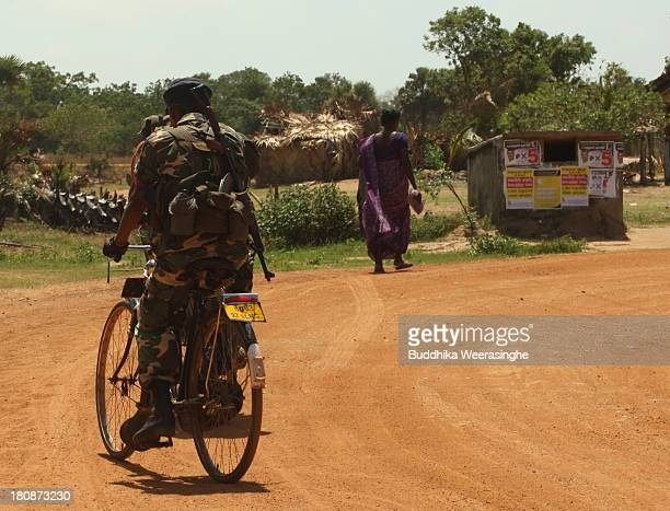 Sri Lankan army soldiers patrol a street as an ethnic Tamil woman walks beside election campaign posters on a wall at a former rebel capital on...