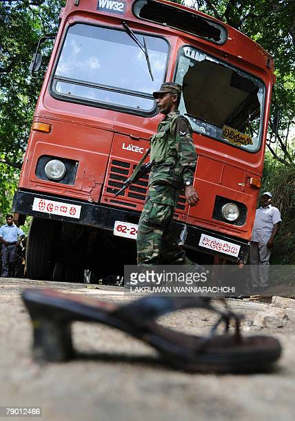 Sri Lankan army soldiers stand alert at the site of a roadside bomb attack on a bus in Buttala some 235 km from Colombo 16 January 2008 At least 24...