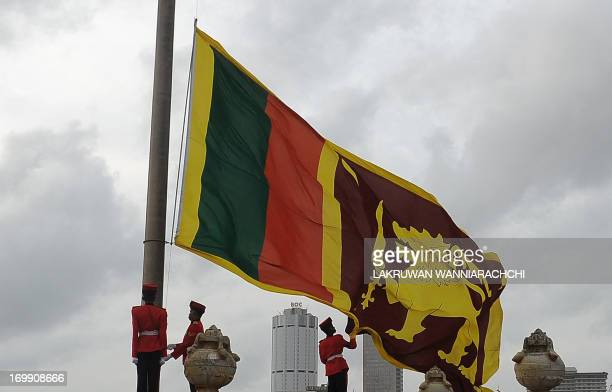 Sri Lankan Army soldiers stand at attention near the Sri Lanka's national flag as it is lowered as part of a daily ceremony at Galle Face Green a...