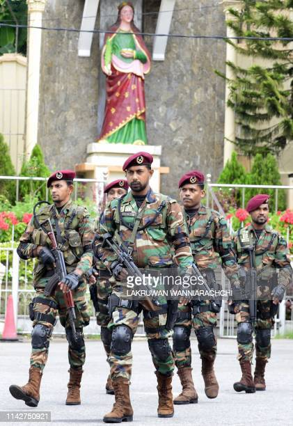 Sri Lankan Army soldiers stand guard at the St Lucia's Cathedral during a holly mass held to bless the victims of Easter Sunday attacks in Colombo on...
