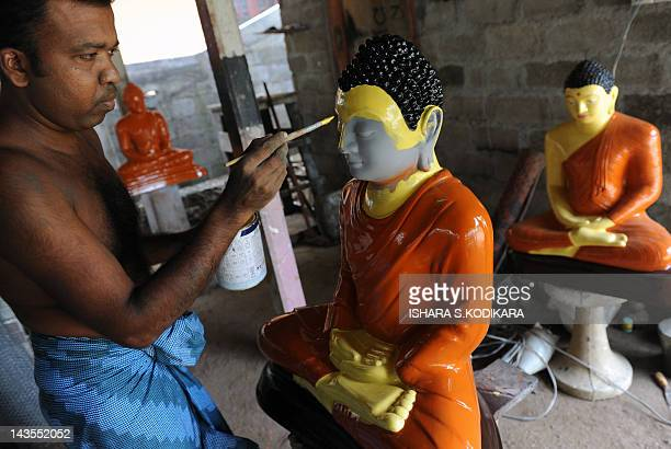 Sri Lankan artisan P. Edirisinghe works on a Buddhist statue in Dompe, on the outskirts of Colombo, on April 29, 2012. Sri Lankan Buddhists are...