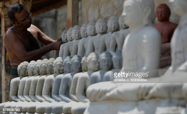 A Sri Lankan artist works on Buddhist statues ahead of the Vesak Festival in Dompe on the outskirts of Colombo on May 7 2017 Sri Lankan Buddhists are...