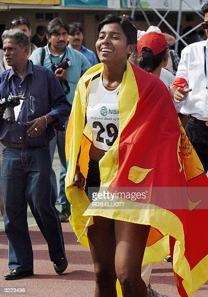 Sri Lankan athlete Sriyani Kulawansa drapes herself in her countries national flag after winning gold in the 100m hurdles female final at the Sport...