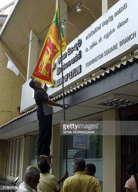 Sri Lankan bank employee places the national flag at halfmast outside a branch in Colombo 31 December 2004 as Sri Lanka declared a day of national...