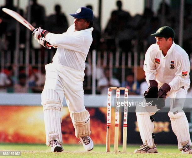 Sri Lankan batsman Arjuna Ranatunga drives the ball as South African wicket keeper Mark Boucher looks on during the final cricket test between Sri...