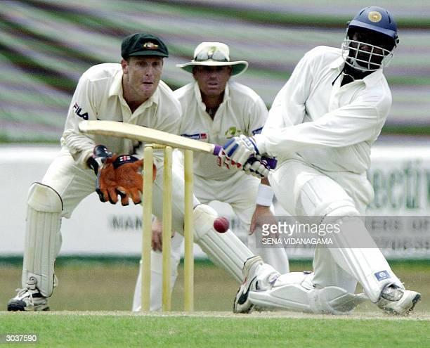 Sri Lankan batsman Avishka Gunawardana sweeps a ball as Australian wicketkeeper Wade Secombe and Shane Warne look on during the practrice match...