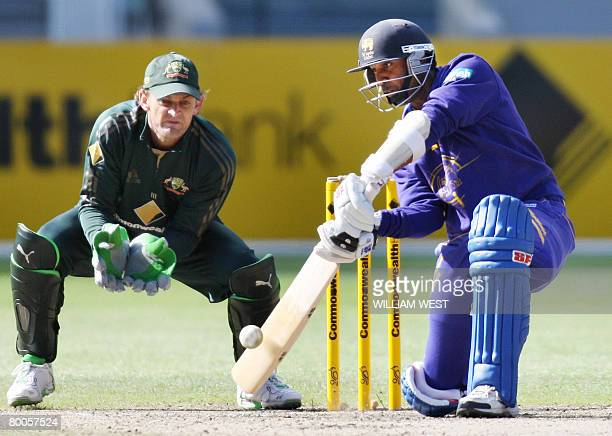 Sri Lankan batsman Chamara Silva drives a ball away as Australian wicketkeeper Adam Gilchrist looks on in their match being played at the MCG in...