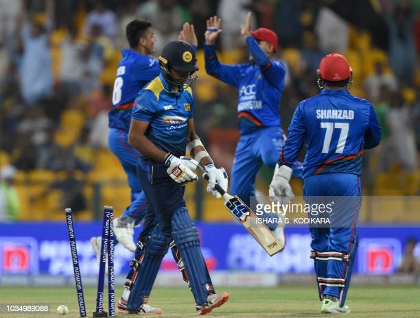 Sri Lankan batsman Dasun Shanaka leaves the field after being dismissed by Afghan cricketer Mujeeb Ur Rahman during the one day international Asia...
