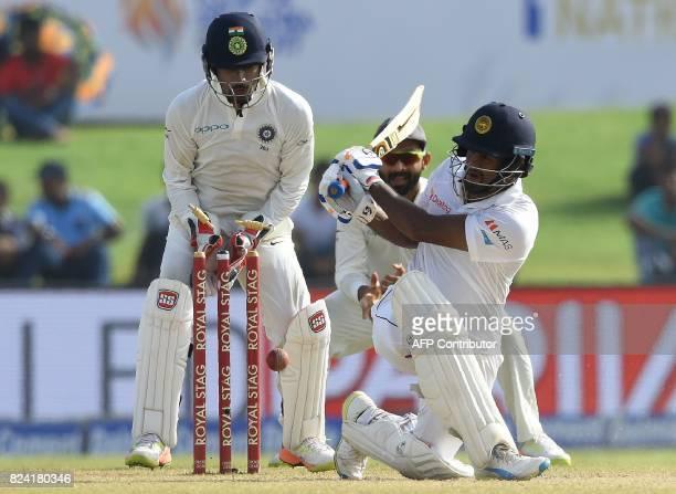 Sri Lankan batsman Dimuth Karunaratne is dismissed by Indian bowler Ravichandran Ashwin as wicketkeeper Wriddhiman Saha looks on during the fourth...