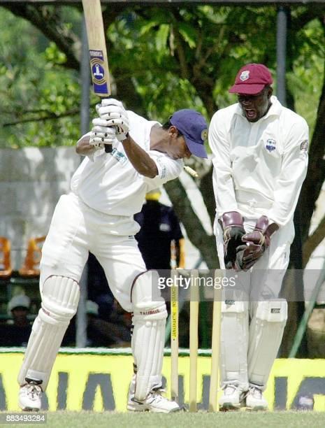 Sri Lankan batsman Kumar Sangakkara is seen being bowled by West Indies bowler Dinanath Ramnarin as West Indies wicketkeeper Ridley Jacobs looks on...