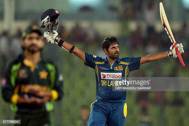 Sri Lankan batsman Lahiru Thirimanne celebrates after scoring a century as Pakistani fielder Fawad Alam claps during the final match of the Asia Cup...