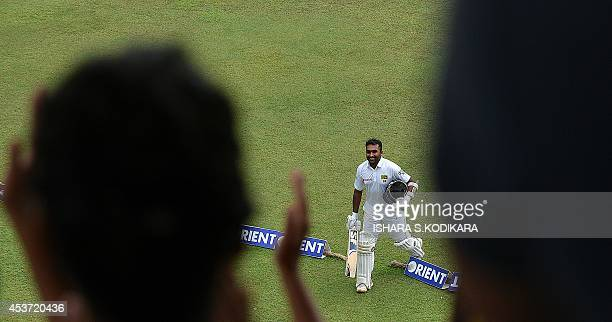 Sri Lankan batsman Mahela Jayawardene raises his bat to the crowd after he was dismissed during the fourth day of the second Test match between Sri...