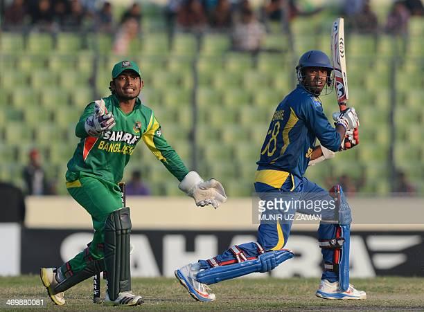 Sri Lankan batsman Sachithra Senanayake plays a shot as Bangladesh wicketkeeper Anamul Haque looks on during the first OneDay International cricket...