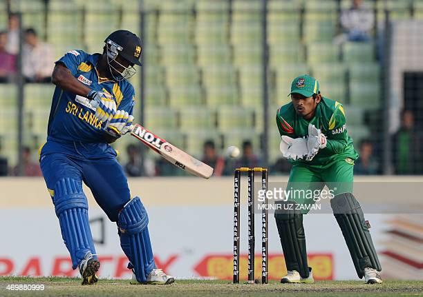 Sri Lankan batsman Thisara Perera plays a shot as Bangladesh wicketkeeper Anamul Haque looks on during the first OneDay International cricket match...
