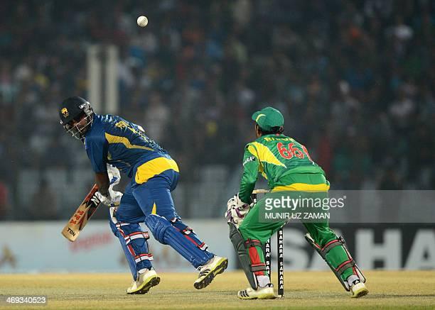 Sri Lankan batsman Thisara Perera plays a shot as Bangladeshi wicketkeeper Anamul Haque looks on during the second T20 cricket match between...