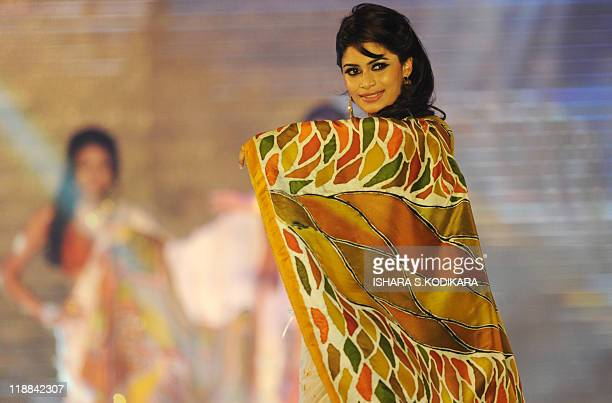 A Sri Lankan beauty pageant contestant parades wearing sari during a glittering contest in Colombo on July 11 2011 The winner will represent Sri...