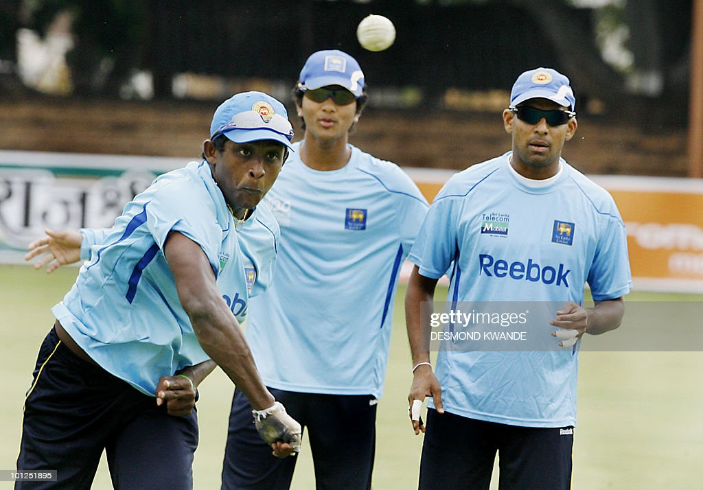 Sri lankan bowler Ajantha Mendis (L) throws the ball while his teammates wicket keeper Dinesh Chandimal (center) and Thilan Samaraweera (R) look on during a practice session in Bulawayo at Queens Sports Club on May 29, 2010.Sri lanka will be playing India on Sunday May 30th 2010 in the second match of the Micromax Cup Triangular One-Day International series that also includes the host Zimbabwe . AFP PHOTO / Desmond Kwande