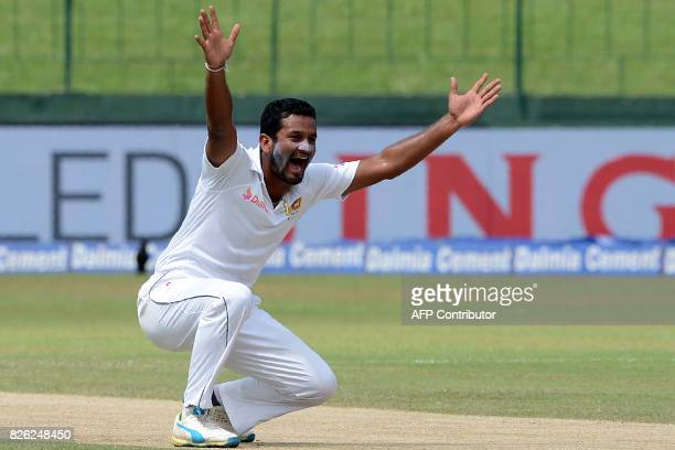 Sri Lankan bowler Dimuth Karunaratne celebrates after he dismissed Indian batsman Cheteshwar Pujara during the second day of the second cricket Test...