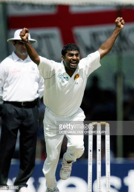 Sri Lankan bowler Muttiah Muralitharan reacts after breaking the world record tally of 708 wickets dismissing the unseen England cricketer Paul...