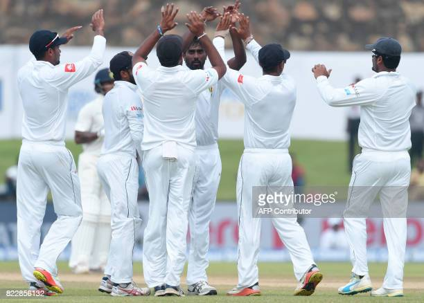 Sri Lankan bowler Nuwan Pradeep celebrates with his teammates after he Indian batsman Abhinav Mukund during the first day of the first Test match...