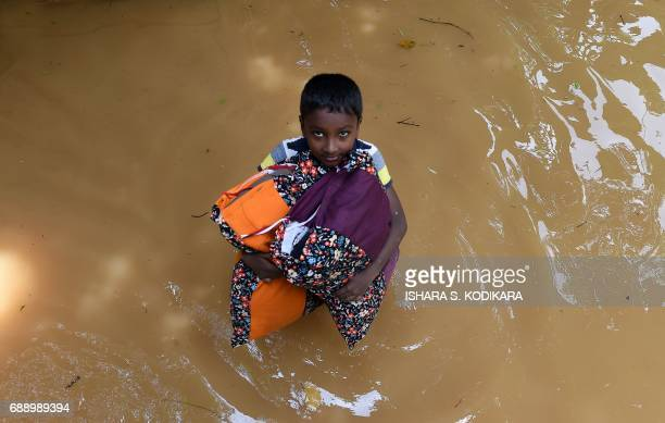 Sri Lankan boy carries pillows through floodwaters from his home in Kelaniya on May 27 2017 Rainfall on May 26 triggered the worst flooding and...