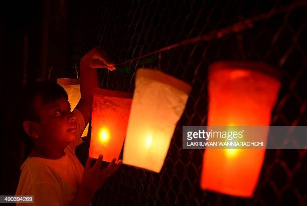 A Sri Lankan boy lights paper lanterns on Vesak day in Colombo on May 14 2014 Sri Lankan Buddhists are preparing to celebrate Vesak which...