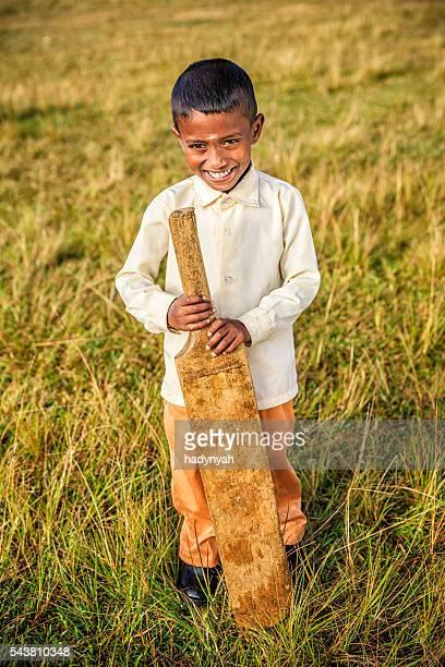 Sri Lankan boy posing with cricket bat on tea plantation