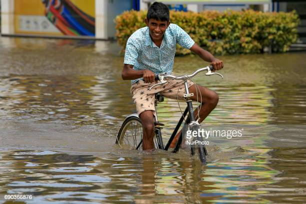 A Sri Lankan boy rides a bicycle across the flooded Southern Expressway at Godagama Matara southern part of Sri Lanka Tuesday 30 May 2017