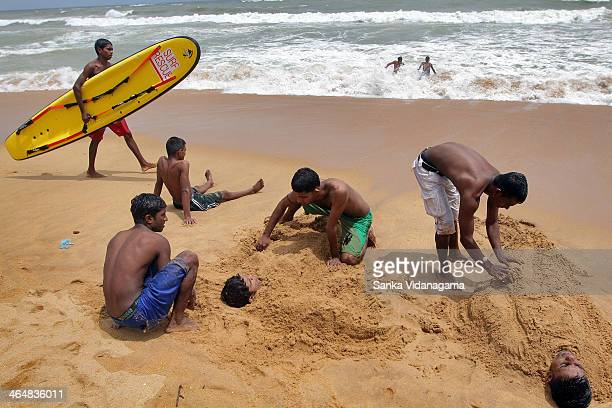 Sri Lankan boys cover sand on their colleagues bodies as a surfer walks along the beach at Mount Lavinia, suburbs of Colombo, on June 09, 2013.