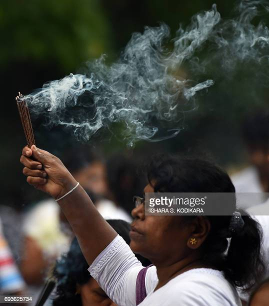A Sri Lankan Buddhist devotee holds incense at the Kelaniya Temple during the Poson festival in the Colombo suburb of Kelaniya on June 8 2017 Sri...