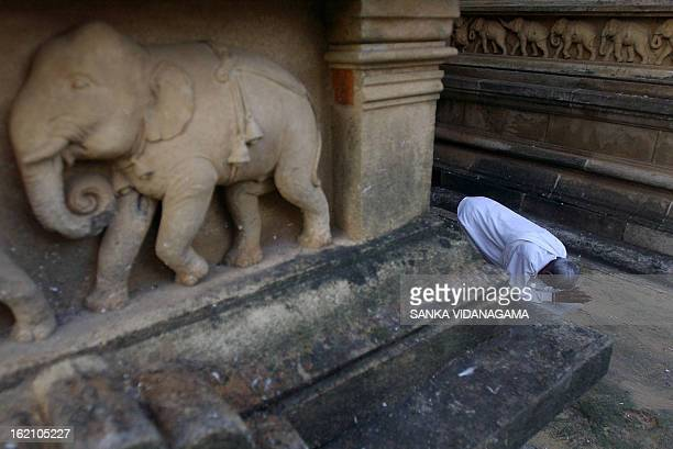 A Sri Lankan Buddhist devotee offers prayers at a temple in Kelanya a suburb of Colombo 25 October 2007 to celebrate Vap Poya or full moon day which...