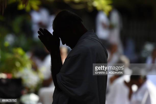 A Sri Lankan Buddhist devotee offers prayers at the Kelaniya Temple during the Poson festival in the Colombo suburb of Kelaniya on June 8 2017 Sri...