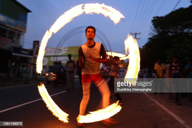Sri Lankan Buddhist devotee spins a fire ring as he performs during a temple festival for marks Poya day or Full Moon Day at a temple on November 22...