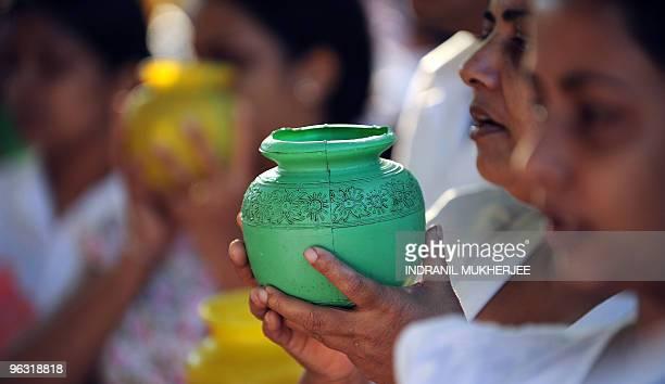 Sri Lankan Buddhist devotees hold water pots as they offer prayers on Poyafull moon at the Kelaniya Temple in Kelaniya Gampaha district on January 29...