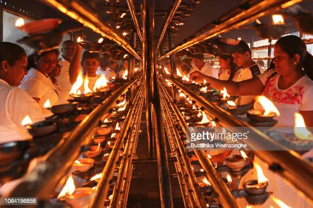 Sri Lankan Buddhist devotees light oil lamps as they mark Poya day or Full Moon Day at a temple on November 22 2018 in Colombo Sri Lanka Buddhists...
