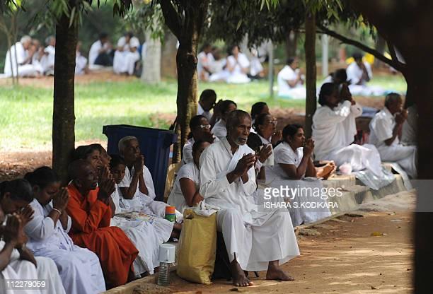 Sri Lankan Buddhist devotees offer prayers during the public holiday Poya Day at the Kelaniya Temple in Kelaniya on April 17 2011 The predominantly...