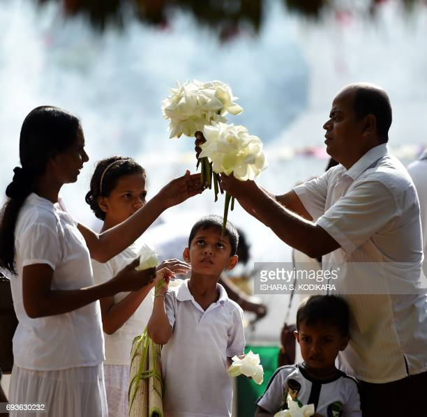 Sri Lankan Buddhist devotees visit Kelaniya Temple to mark the Poson Festival in the Colombo suburb of Kelaniya on June 8 2017 Sri Lanka celebrates...