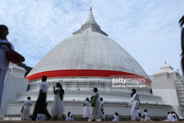 Sri Lankan Buddhist devotees walk around a pagoda and pray as they mark Poya day or Full Moon Day at a temple on November 22 2018 in Colombo Sri...