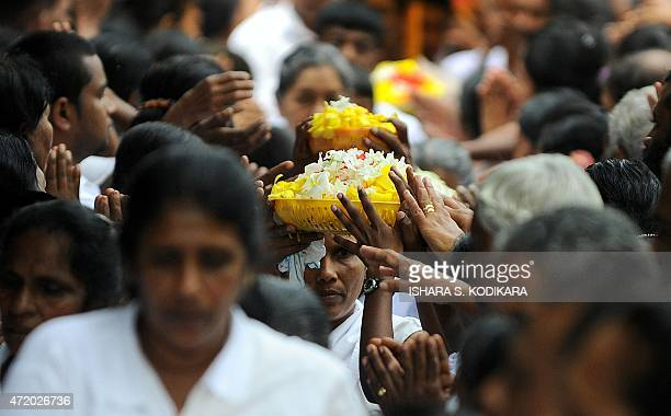 Sri Lankan Buddhists pray at a temple during the Vesak Festival at the Kelaniya temple in Kelaniya on May 3 2015 Sri Lankan Buddhists are preparing...