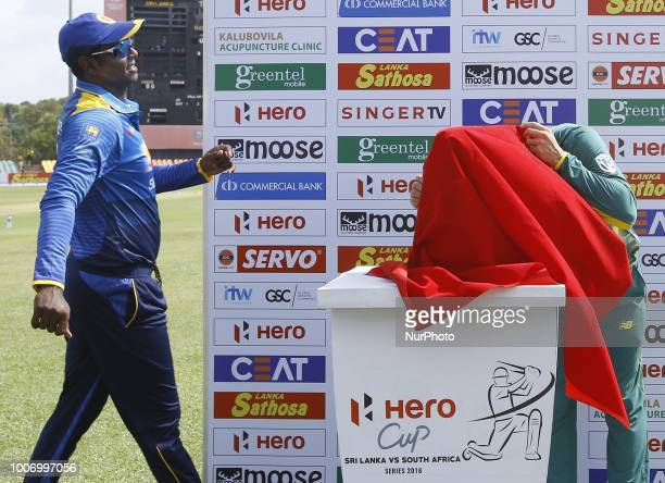 Sri Lankan captain Angelo Mathews looks on as South African captain Faf Du Plessis looks at the trophy hidden under a cloth during the 1st One Day...