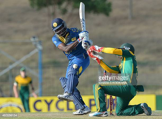 Sri Lankan captain Angelo Mathews plays a shot as South African wicketkeeper Quinton de Kock looks on during the third and final One Day...