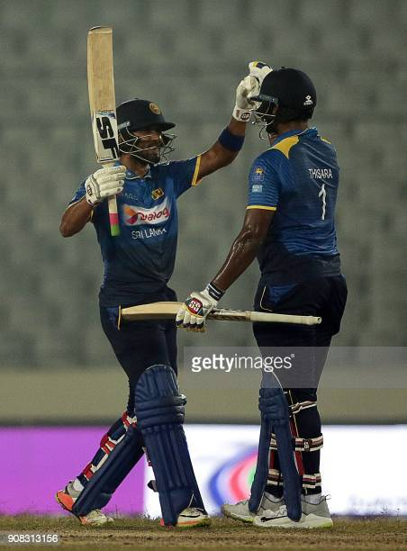 Sri Lankan captain Dinesh Chandimal and Thisara Perera celebrate after five wickets victory during the Fourth One Day International cricket match in...