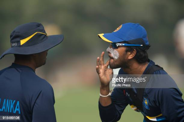 Sri Lankan captain Dinesh Chandimal applies sun cream on his face watching through fielding coach Manoj sun glasses during a training session ahead...