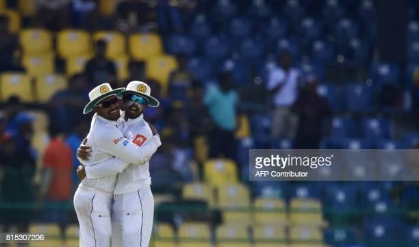 Sri Lankan captain Dinesh Chandimal celebrates with his teammates Danushka Gunathilaka after he dismissed Zimbabwe's cricketer Peter Moor during the...