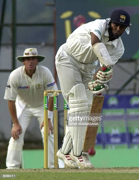 Sri Lankan captain Hashan Tillakaratne bats as Australian fielder Shane Warne looks on during the first day of the second test match between...
