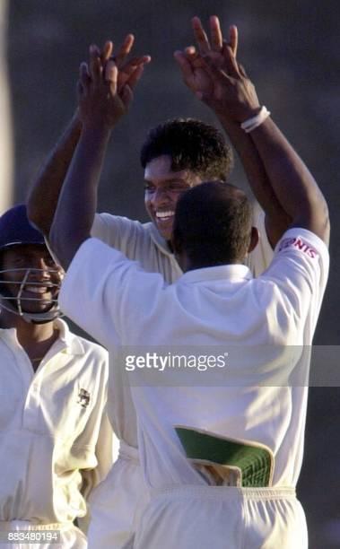 Sri Lankan captain Sanath Jayasuriya celebrate with pace bowler Dilhara Fernando as Sri Lankan wicketkeeper Kumar Sangakkara looks on after Fernando...
