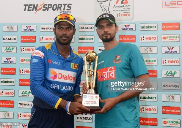 Sri Lankan captain Upul Tharanga and Bangladesh cricket captain Mashrafe Mortaza poses with the series trophy after the third and final one day...