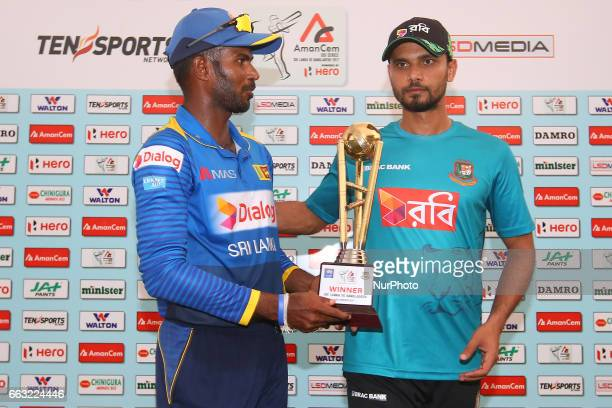 Sri Lankan captain Upul Tharanga and Bangladeshi captain Mashrafe Mortaza walk away after posing with the trophy following a series level for the...