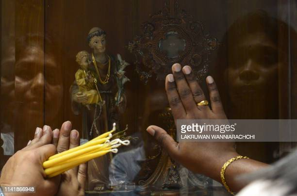 Sri Lankan Catholic devotees pray at St. Anthony's church after it was partially opened for the first time since the Easter Sunday attacks in Colombo...